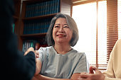 Happy Asian senior couple feel releif and pleasant after get the advice about family financial planning from professional financial advisor at home.