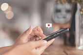 Woman hand using smartphone with heart icon at coffee shop background. Technology business and social lifestyle concept.