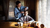 Portrait of poor woman cutting daughter's hair indoors at home, poverty concept.