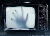 Old black  scary haunted tv set with ghost hand on a screen.