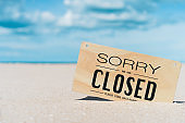 Closed sign on tropical sand beach with blue sky background. Summer vacation and travel holiday concept.