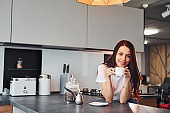 With cup of fresh coffee. Young beautiful brunette in casual clothes indoors in kitchen at daytime