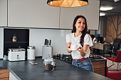 Gives fresh coffee. Young beautiful brunette in casual clothes indoors in kitchen at daytime
