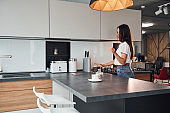 Young beautiful brunette in casual clothes preparing coffee in kitchen at daytime