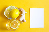 Medicinal tea in a cup, ginger, lemon-strengthen the immune system in the cold season and copy space, sheet for notes. Vitamin drink for health and ingredients on a yellow illuminating background.