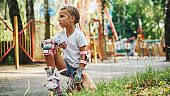 Sits on the green grass. Cheerful little girl on roller skates have a good time in the park near attractions