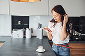 Young beautiful brunette in casual clothes indoors in kitchen at daytime using smartphone