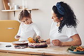 Senior woman with her granddaughter preparing dietical cake on kitchen