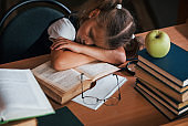 Sleeping on the table. Cute little girl with pigtails is in the library. Apple on the books