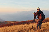 Male photographer standing and working at majestic landscape of autumn trees and mountains by the horizon