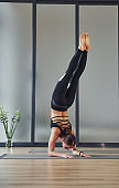 Doing headstand. Young woman in sportive wear and with slim body have fitness yoga day indoors