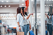 Looking through the glass. Two young women have a shopping day together in the supermarket