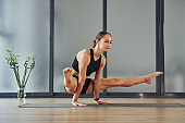 Difficult exercise. Young woman in sportive wear and with slim body have fitness yoga day indoors