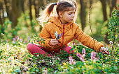 Happy little girl in casual clothes sitting in spring forest at daytime