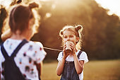 Two female kids stands in the field and talking by using string can phone