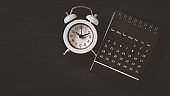 white analog clock and black calendar on grunge black paper background , business , time passing , appointment, due date concept with copy space
