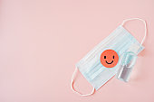 pink healthy smiling face paper cut on medical face mask and bottle of blue alcohol gel on sweet pink background, campaign for wearing mask, awareness to protect ourself from corona virus, new normal