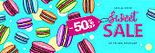 Colorful summer big sale poster with sweet macaron cakes.  French macaroons. Junk food background.