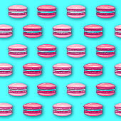 Seamless pattern of pink sweet macarons cakes on blue background. French macaroons. Junk food background