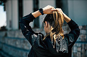 Rear view of young attractive, fit caucasian female runner standing in the urban exterior and tying ponytail.