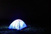 Illuminated blue tent at night under starry sky. Traveling and camping concept