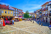 people tourists walking down cobblestone square with traditional multicolored houses in Guimaraes city historical centre