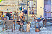 blacksmith man forging iron metal in cobblestone square with medieval houses and buildings