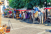 rider warrior on horse and women in old traditional clothes in cobblestone square in historical town centre, medieval scene