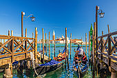 Gondolas moored docked at wooden pier in water of San Marco basin