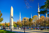 Sultan Ahmed Mosque Blue Mosque with minarets, Obelisk of Theodosius Dikilitas and tourists walking down pedestrian street