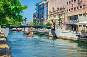 Aveiro cityscape with traditional colorful Moliceiro boat with tourists sailing in narrow water canal