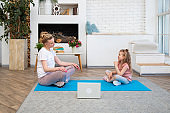 Portrait of mother with her preschool-aged caucasian daughter doing yoga online using laptop sitting in lotus position on yoga mat in their living room