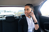 Businesswoman talking on phone in car.