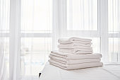 Stack of fresh white bath towels on bed sheet in modern hotel bedroom interior with window on background, copy space
