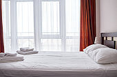Hotel bedroom interior with empty double bed with wooden headboard and big window, copy space. White sheet, soft pillows and towels on bed, side view