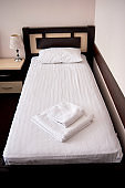 Stack of white clean bath towels on bed sheet in modern hotel bedroom interior, copy space. Empty single bed with wooden headboard and bedside table