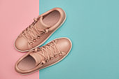 Stylish pink female shoes on pastel background, copy space. New sneakers on pink and blue background. Beauty and fashion concept. Flat lay, top view. Overhead shot
