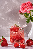 Fresh strawberry lemonade in sparkling glasses and rose in vase on gray table background, copy space. Cold summer drink. Berry cocktail. Splash