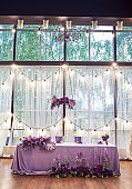 Wedding presidium in restaurant, copy space. Banquet table for newlyweds with flowers, monstera leaves, violet cloth and bulbs. Lush floral arrangement. Luxury wedding decorations