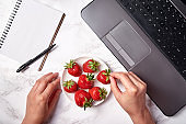 Top view of woman hands, laptop computer, blank notebook and strawberries on table, copy space. Freelancer workspace, home office. Top view, flat lay