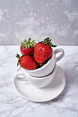 Ripe organic strawberries in white ceramic cup on gray marble background, copy space. Healthy food concept, creative still life