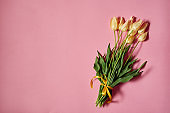 Bouquet of yellow tulips on pink pastel background, copy space. Spring minimal concept. Womens Day, Mothers Day, Valentine's Day, Easter, birthday. Nature background. Flat lay, top view
