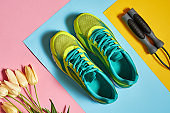Pair of sport shoes, skipping rope and tulips bouquet on colorful pastel background. New sneakers on pink, blue and yellow paper, copy space. Overhead shot of running foot wear. Top view, flat lay