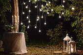Night wedding ceremony with candles, lanterns and bulb lights on tree outdoors, copy space