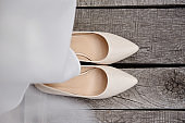 Beautiful beige female shoes and wedding dress on wood background outdoors, copy space