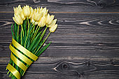 Spring background with bunch of tulips with ribbon, copy space. Yellow tulips on wooden background. Flat lay, top view. Holiday greeting card for Valentine's Day, Woman's Day, Mother's Day, Easter