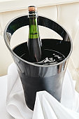 Bottle of cold wine or champagne in ice bucket on white table at hotel room, copy space. Wedding reception, holiday concept