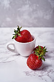 One big organic strawberry in white ceramic coffee cup on gray marble background, copy space. Healthy food concept, creative still life, close up