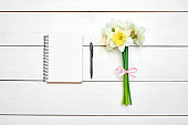 Bouquet of daffodils (narcissus) and blank notebook with pen on white wooden background, copy space. Top view, flat lay. Spring flowers. Greeting card for March 8 (Womens Day), Mothers day. Easter