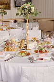 Table setting with blank guest card, white plate with pink napkin, cutlery and flowers on table, copy space. Place setting at wedding reception. Table served for wedding banquet in restaurant